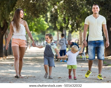 Young parents holding little kids in park at summer day. Focus on man