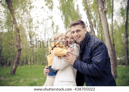 young parents holding the girl in his arms, smiling - stock photo