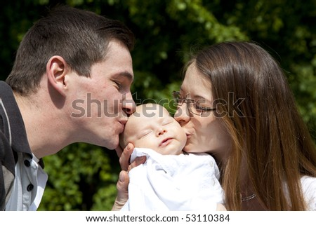 young parents kissing her sleeping 7 weeks old daughter