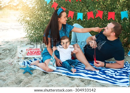 young parents playing with their child sitting on the beach - stock photo