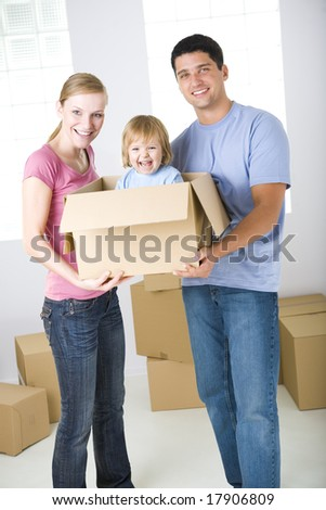 Young parents standing between cardboard boxes. They're holding one box with their daughter. They're looking at camera. Front view. - stock photo
