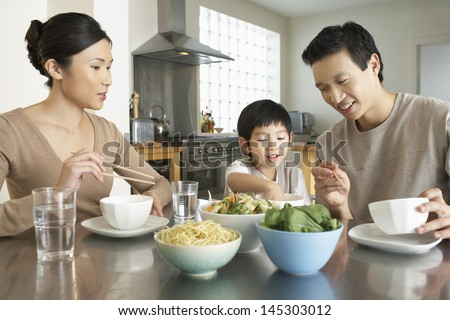 Young parents watching son stick hand in bowl at kitchen table during meal - stock photo