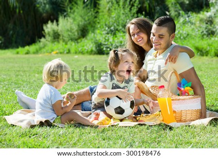 Young parents with children having picnic outdoor on sunny day - stock photo