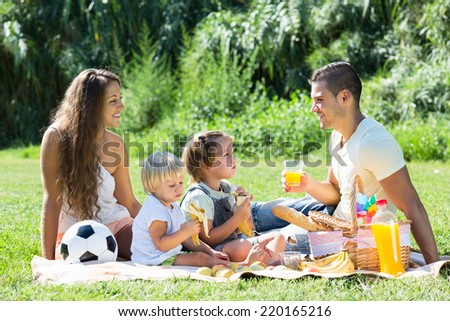 Young parents with little daughters having holiday with picnic
