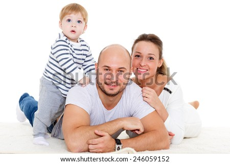 Young parents with lovely son lie on a white background. Happy family.