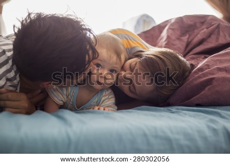 Young Parents With Their Son In Bed Spending Lovely Morning - stock photo