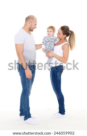 Young parents with their  sweet  child stand on a white background. Happy family.