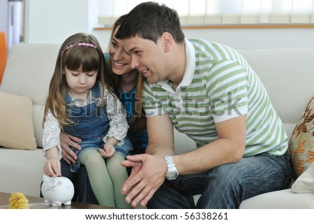 young parrent at home with beautiful child make savings and put coins money in piggy bank - stock photo