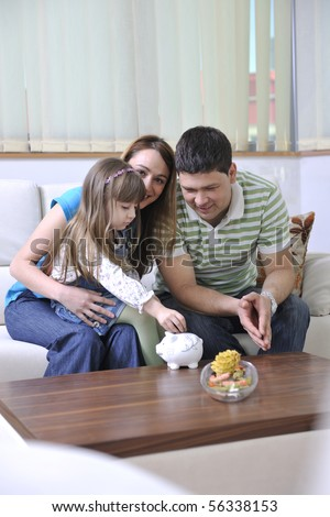 young parrents at home with beautiful child make savings and put coins money in piggy bank