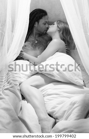 Young passionate couple making romantic love in bed - stock photo