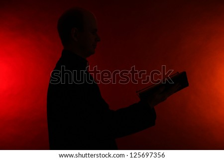 Young pastor with Bible, on dark red background - stock photo