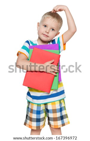 Young pensive boy in striped shirt with books on the white background - stock photo