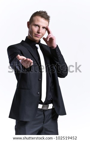 Young pensive business man pointing at something interesting on - stock photo