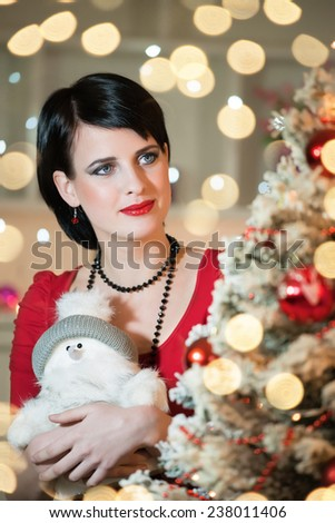 Young, pensive woman looking at the Christmas tree.Bokeh light, shallow doff - stock photo