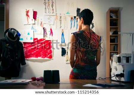 Young people and small business, hispanic woman at work as fashion designer and tailor, looking at sketches of new collection in atelier - stock photo