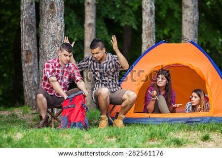 Young people angry at their friend because he forgot the most important thing for camping - stock photo