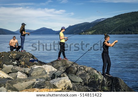Young people are fishing on the rocks next to the fjord, Norway