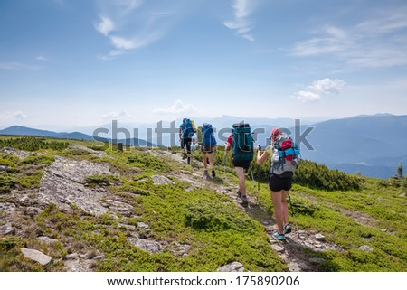 Young people are hiking in Carpathian mountains in summertime - stock photo