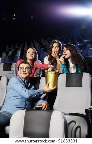 Young people at cinema eat pop-corn - stock photo