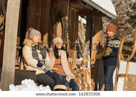 Young people by wooden winter cottage enjoying sunshine outdoor - stock photo