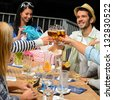 Young people celebrating birthday toasting with beer outdoors - stock