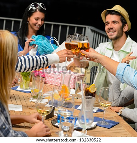 Young people celebrating birthday toasting with beer outdoors - stock photo
