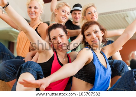 young people dancing in a studio or gym doing sports or practicing a dance number - stock photo