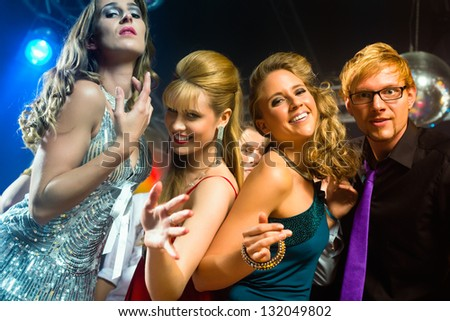 Young people dancing in club or disco and have party; the girls and boys, friends, having fun - stock photo