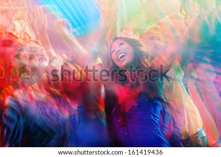 Young people dancing in club or disco party, the girls and boys, friends, having fun - stock photo