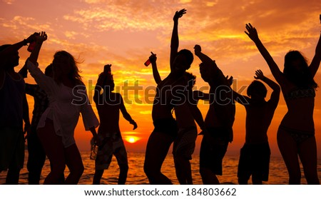 Young People Dancing On Beach at Sunset - stock photo