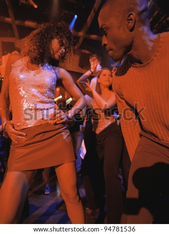 Young people dancing together at club - stock photo