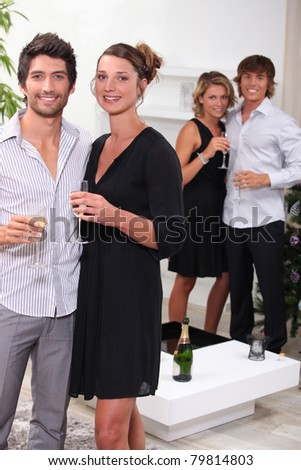 Young people drinking champagne at Christmas - stock photo