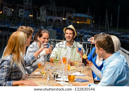 Young people drinking shots at outside bar night out - stock photo