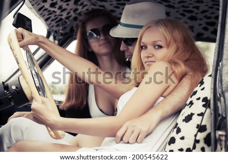 Young people driving retro car - stock photo