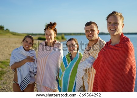 Young people drying off in colorful beach towels