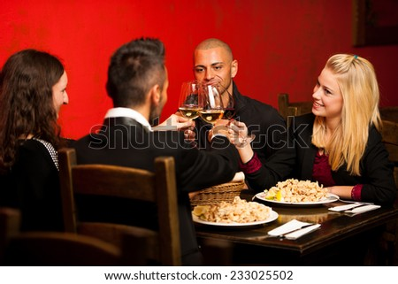 Young people eat dinner at restaurant - stock photo