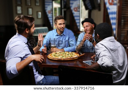Young people eating pizza and drinking beer in cafe - stock photo