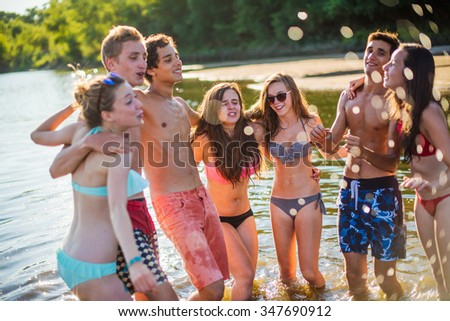 Young people enjoying the sun during a sunny day at the beach. They are on summer break, standing arm in arm with their feet in the water, wearing trendy swimsuits and sunglasses - stock photo