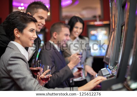 Young people enjoying to play slot machines at casino - stock photo