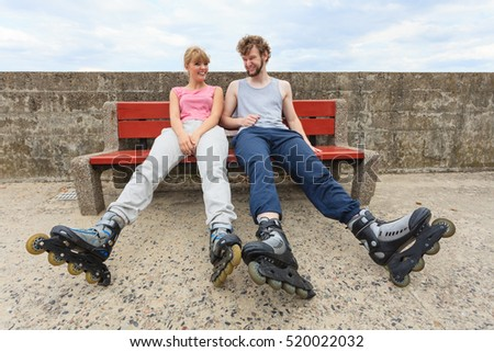 Young people friends with roller skates. Woman and man relaxing on bench outdoor.