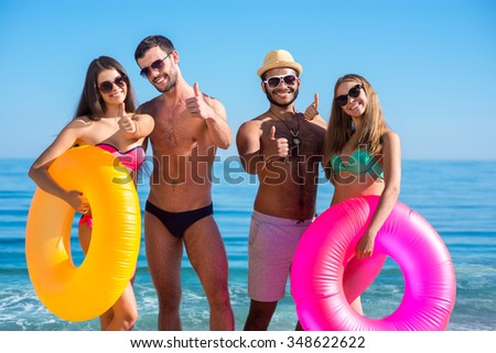 Young people having fun on the beach. Guys and girls sunbathing on the sea. Funny students. Luxury vacation on the islands. Show a thumbs up.