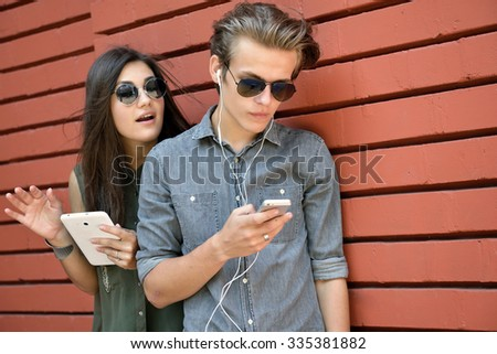 Young people having fun outdoor using gadgets against red brick wall. Urban lifestyle, internet and gadget dependence, friends, social network concept. Image toned and noise added. - stock photo