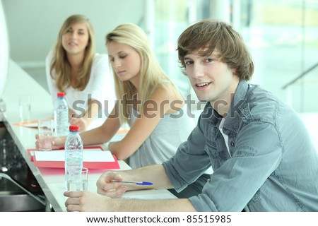 Young people in a bar with coursework and bottles of water