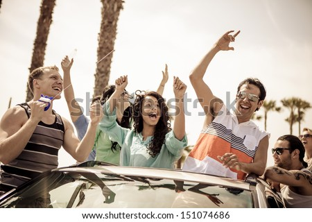 Young People in a car having fun on a Road trip - stock photo