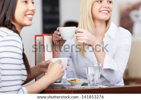 young people in cafe sitting at table and relaxing with a cup of coffee - stock photo