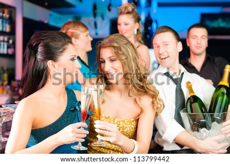 Young people in club or bar drinking champagne and having fun - stock photo