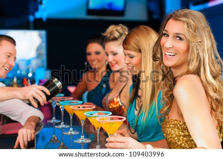 Young people in club or bar drinking cocktails and having fun; the barkeeper is mixing drinks - stock photo