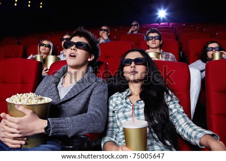 Young people in 3D glasses hard watching a movie at the cinema - stock photo