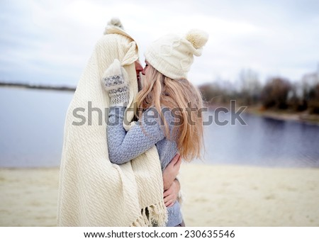 young people in love gently embrace on a beach