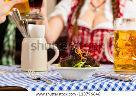 Young people in traditional Bavarian Tracht eating in restaurant or pub lunch or dinner, focus on salad in the foreground - stock photo
